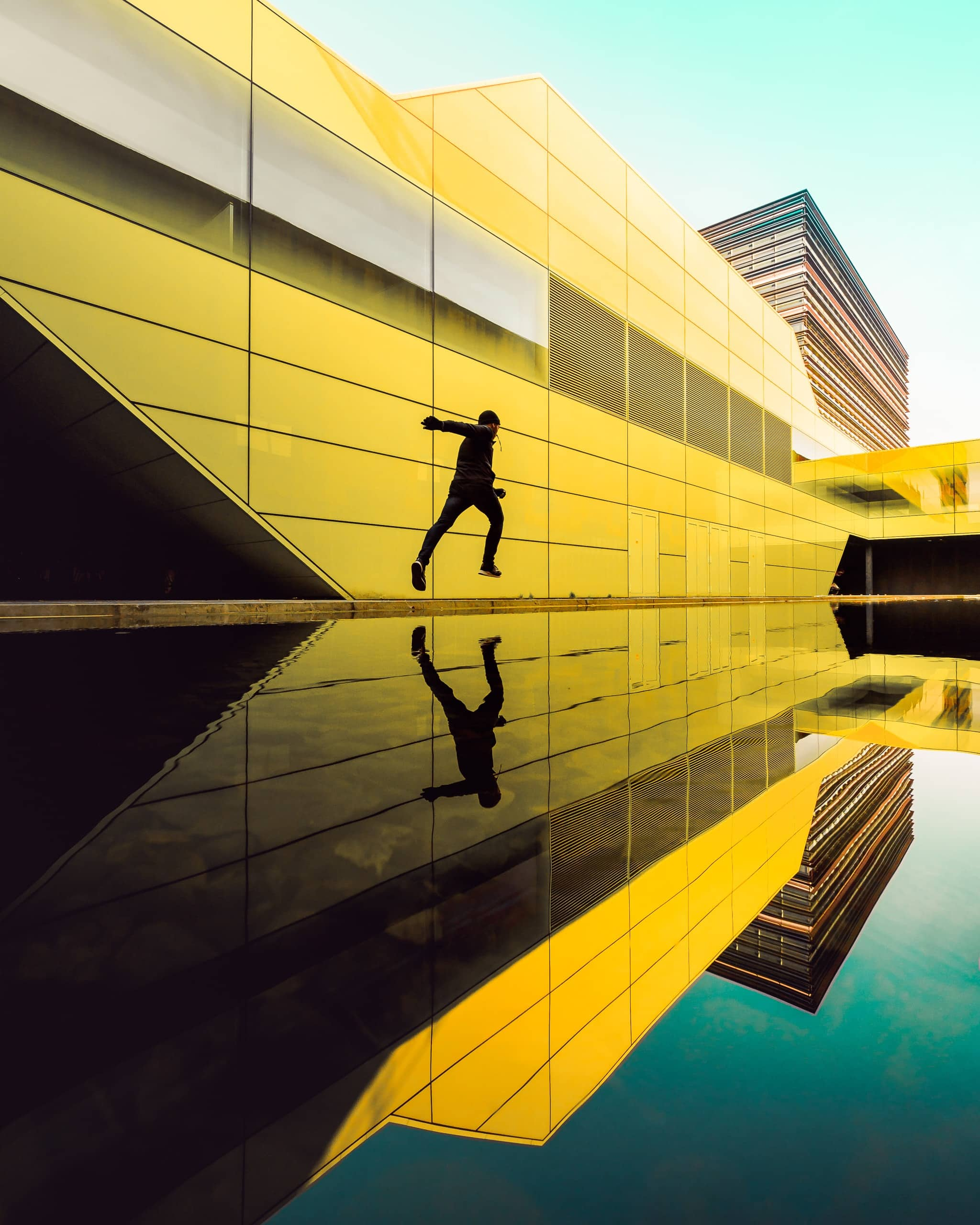 Reginar Photography running through Utrecht Science Park architecture with reflection of the buildings with yellow and green color palette