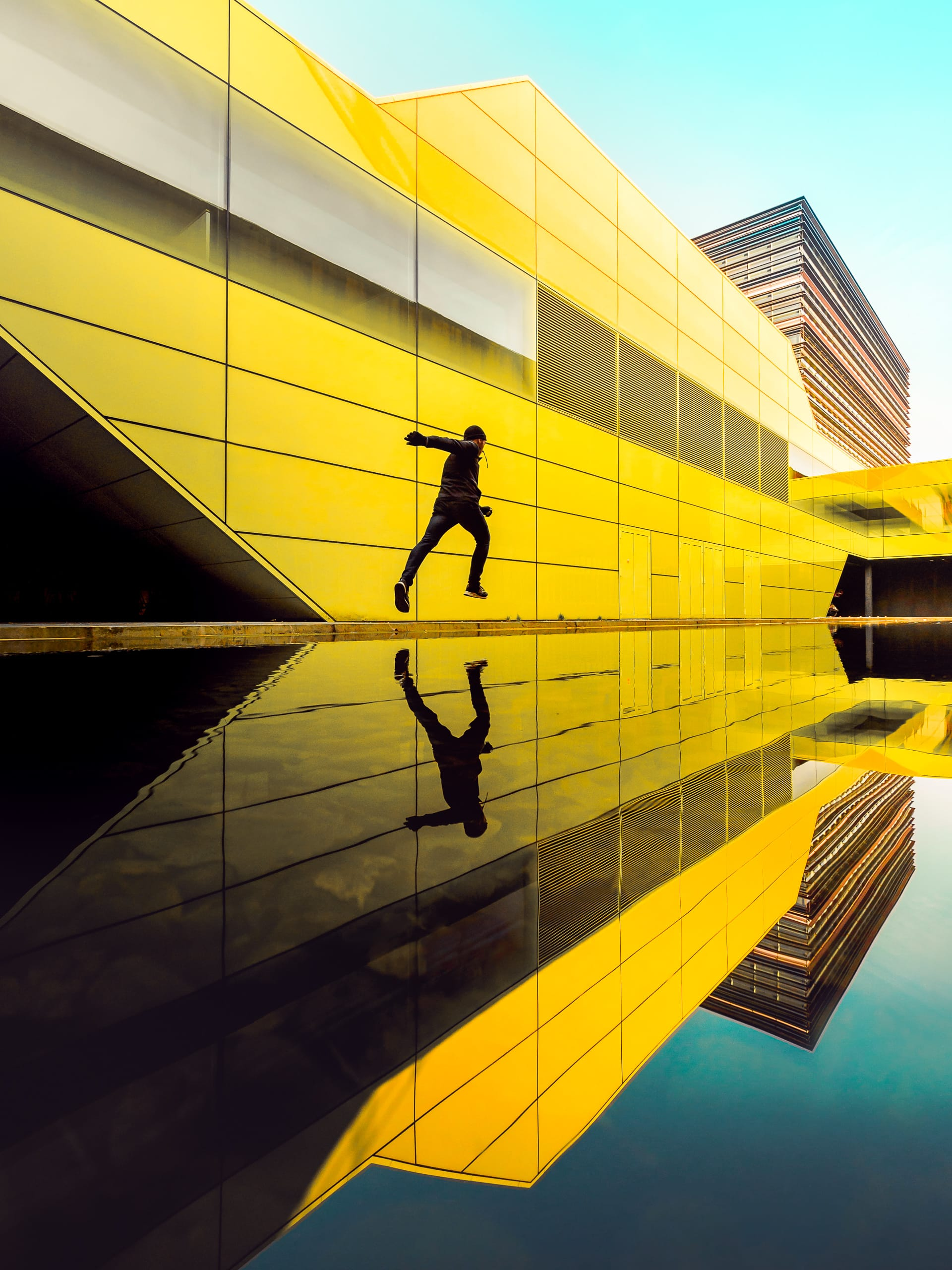 Man running in black clothes through colorfull modern architecture urban environment